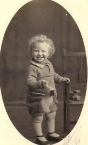 To år gammel poserer unge Arne med sit brede smil og store krøllede hår. På det tidspunkt vidste han ikke, at hans tip-oldefar var en tapper helt, der egenhændigt nedlagde en kronhjort - eller var det et vildsvin - kun bevæbnet med en jagtkniv. Tip-oldefar var ansat hos Greven af Weddellsborg, og han havde blandt andet til opgave at samle vildt efter grevens årlige jagter. Ved en ad disse lejligheder blev Tip-oldefar angrebet af et anskudt dyr, som han dræbte - næsten med de bare næver. Derfor blev han af Greven begavet med en landsby, nemlig Faurskov, som hurtigt blev befolket med Skjelsager-slægtens børn og børnebørn. Og det var her, at den unge Arne blev foreviget i 1929.