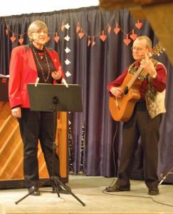 """Vore egne visesangere viste igen deres kunst til glæde for de mange medlemmer, der hyggede sig på Ellegården den 12. december 2014. Her er det Mette og Per, der underholder med """"Digterjul"""" skrevet og komponeret af Ida & Bent From. Inden da, havde de sunget en ny og interessant fortolkning af Bjarne Høyers og Erik Leths """"Skal vi klippe vore julehjerter sammen"""" (Foto: John Stæhr)"""